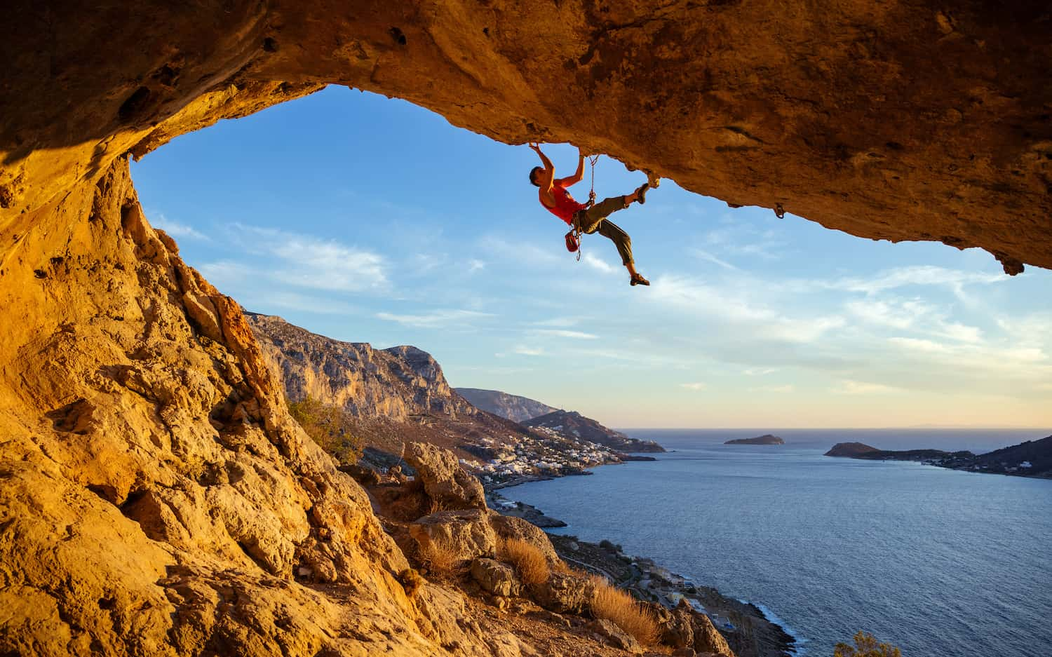 Rock climber hanging above the sea